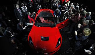 Journalists surround General Motors' 2014 Chevrolet Corvette Stingray on Sunday, Jan. 13, 2013, the night before press days at the North American International Auto Show in Detroit. (AP Photo/Paul Sancya)