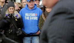 "Bill Pahlck wears a ""Restore The Shore"" sweatshirt Wednesday morning as he and others in Belmar, N.J., listen to Gov. Chris Christie describe rebuilding plans. The governor helped Belmar officials kick off construction of a 1.3-mile boardwalk to replace the one destroyed by Superstorm Sandy in October. (Associated Press)"