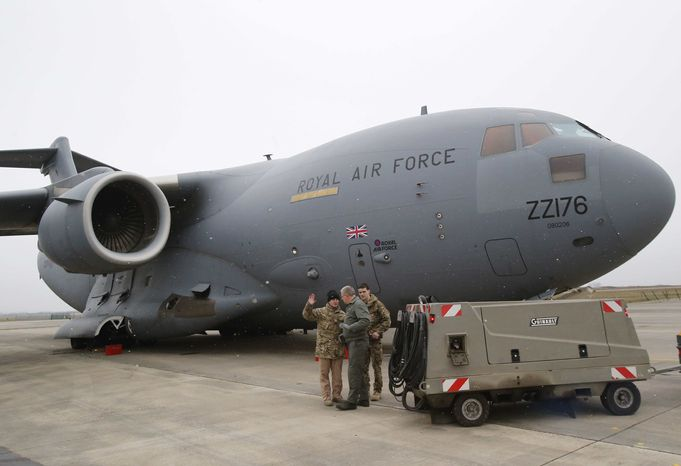A French airman, center, talks to British military personnel prior to the take off a British C17 transport plane enroute to Mali at the French army base in Evreux, 90