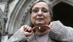 ** FILE ** This Tuesday, Jan. 19, 2010, file photo shows British Airways check-in employee Nadia Eweida displaying her cross to the media as she arrives at the Royal Courts of Justice to fight a ruling that she was not a victim of religious discrimination by British Airways. (AP Photo/Sang Tan, File)
