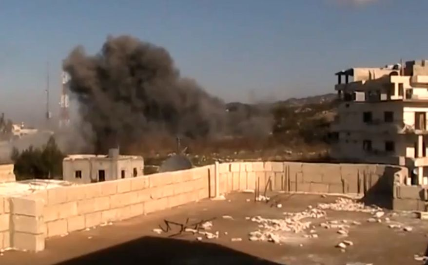 Smoke rises from buildings in Latakia, Syria, after heavy shelling on Monday, Jan. 14, 2012, in this image taken from video that has been authenticated based on its contents and other AP reporting. (AP Photo/Shaam News Network via AP video)