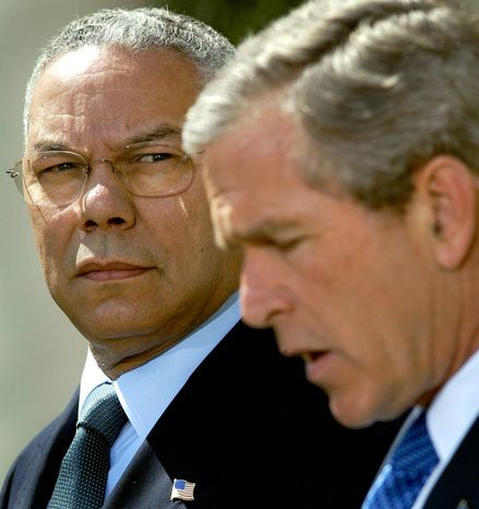 Secretary of State Colin Powell looks April 4, 2002, on as President Bush makes a statement in the Rose Garden of th