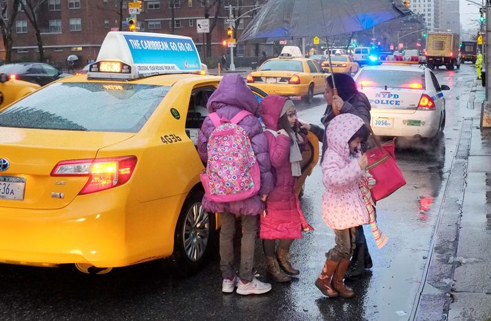A woman takes her children by taxi to Public School 33 in New York on Wednesday as more than 8,000 school bus drivers and aides go on strike over job protection. Children who