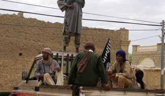 Fighters from the al Qaeda-linked Ansar Dine stand guard in Timbuktu, Mali, as they prepare to publicly lash a member of the Islamic Police found guilty of adultery. (Associated Press)