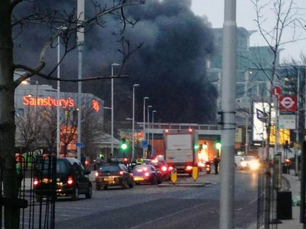 Smoke billows from the scene following a helicopter crash in central London, after it hit a crane on St. George's Tower building in the Vauxhall area of central London, Wednesday Jan. 16, 2013. Police say two people were killed when a helic