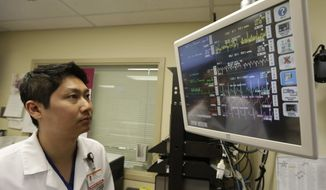 In this Monday, Jan. 14, 2013, photo, Dr. Steve Sun looks over a heart monitor display in the emergency room at St. Mary's Medical Center in San Francisco. A new government report shows the number of people seeking emergency treatment after consuming energy drinks has doubled nationwide over the last four years. (AP Photo/Eric Risberg)
