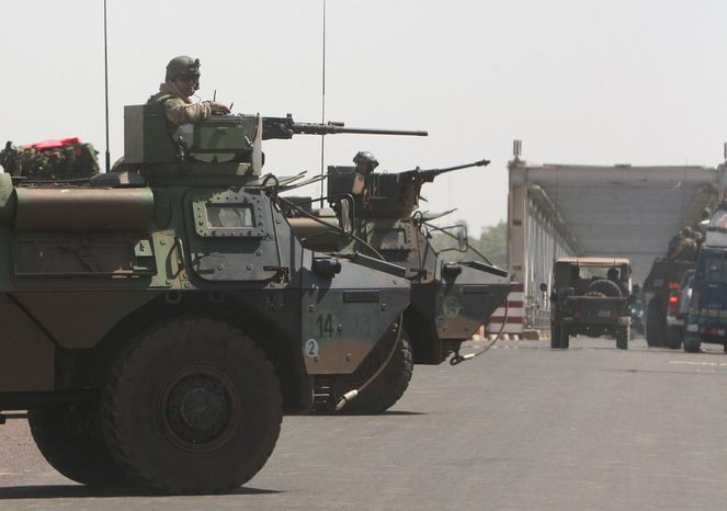 """French troops stand guard along the road leading from Markala to Niono in central Mali on Wednesday as they pressed northward toward territory occupied by radical Islamists. In announcing the start of the land assault, military officials said soldiers would be in direct combat """"within hours."""" (Associated Press)"""