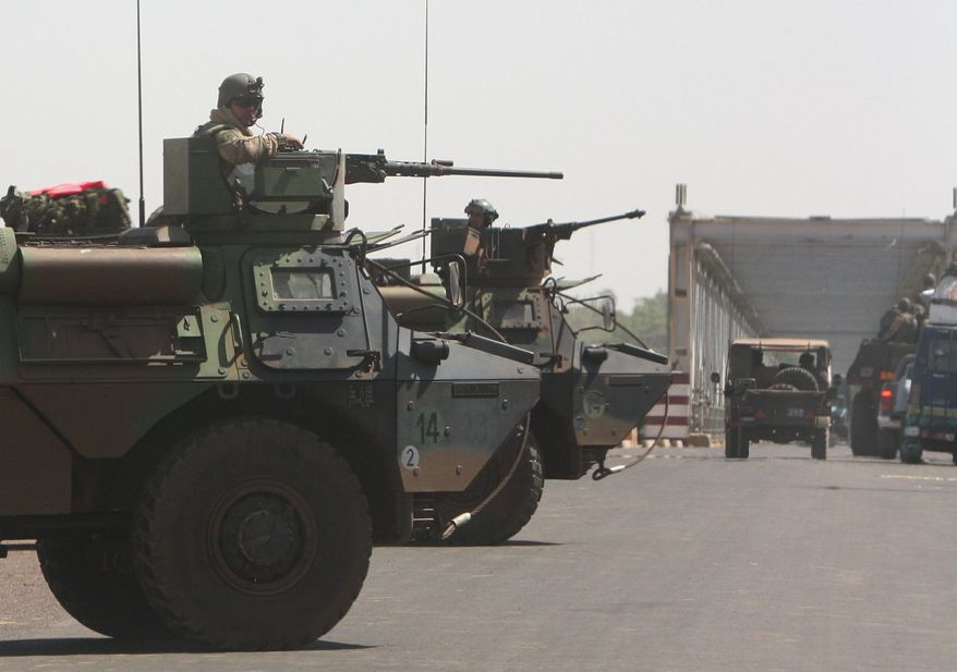"French troops stand guard along the road leading from Markala to Niono in central Mali on Wednesday as they pressed northward toward territory occupied by radical Islamists. In announcing the start of the land assault, military officials said soldiers would be in direct combat ""within hours."" (Associated Press)"