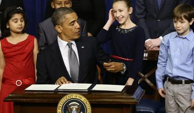 From left: Hinna Zeejah, 8, Taejah Goode, 10, Julia Stokes, 11, and Grant Fritz, 8, who wrote letters to President Obama about the school shooting in Newtown, Conn., watch as the president jokes about being left handed as he signs executive orders outlining proposals to reduce gun violence on Jan. 16, 2013, at the White House. (Associated Press))