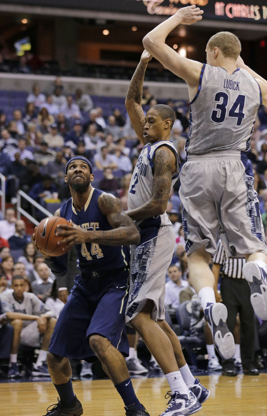 Pittsburgh forward J.J. Moore (44) looks to shoot as he guarded by Georgetown forwards Greg Whittington (2) and Nate Lubick (34) during the first half of an NCAA college basketball game, Tuesday, Jan. 8, 2013, in Washington. (AP Photo/Alex Brandon)