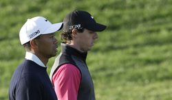 Rory McIlroy from Northern Ireland, right, and Tiger Woods from U.S. walk on the 13th hole during the first round of Abu Dhabi Golf Championship in Abu Dhabi, United Arab Emirates, Thursday, Jan. 17, 2013. (AP Photo/Kamran Jebreili)