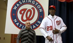 **FILE** Washington Nationals general manager Mike Rizzo (left) looks on as newly acquired pitcher Rafael Soriano models his jersey during an introductory news conference at Nationals Park in Washington on Jan. 17, 2013. Rizzo also discussed the three-team trade that sent Michael Morse to the Seattle Mariners in exchange for pitching prospect A.J. Cole from the Oakland Athletics. (Associated Press)