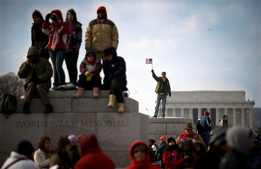 ** FILE ** A man waves a flag from atop part of the World War II Memorial after the swearing in of President Barack Obama on inauguration day on the National Mall in Washington D.C., Tuesday, Jan. 20, 2009. (Allison Shelley / The Washington Times)