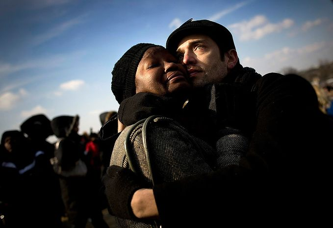 """Married coule Joe Savage and Devan Southerland of Baltimore embrace after the swearing in of President Barack Obama on inauguration day on the National Mall in Washington D.C., Tuesday, Jan. 20, 2009.  """"I never ever thought we'd see this day,"""" said Savage. (Allison Shelley / The Washington Times)"""