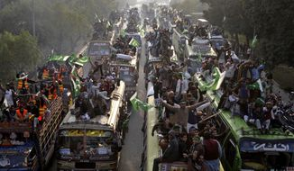 ** FILE ** Supporters of Pakistani Sunni Muslim cleric Tahir-ul-Qadri, 61, march toward the capital Islamabad, Pakistan, Sunday, Jan 13, 2013, in Pakistan. (AP Photo/K.M. Chaudary)