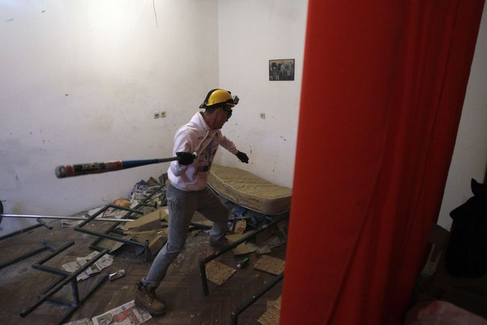 In this Dec. 27, 2012, photo visitor Savo Duvnjak smashes furniture and other household items during a demolishing session at the Rage Room, in Novi Sad, Serbia. (AP Photo/Dar