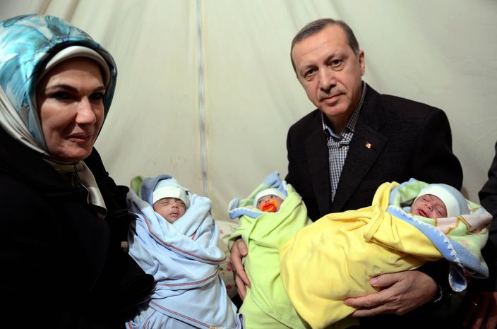 ** FILE ** In this photo provided by Turkish Prime Minister's Press Service, Turkish Prime Minister Recep Tayyip Erdogan, and his wife Emine Erdogan hold newly born babies during a visit to a Syrian refugee camp in Sanliurfa, Turkey, Sunday, Dec. 30, 2012. Erdogan repeated a call on Syrian President Bashar Assad to step down. (AP Photo/Kayhan Ozer)