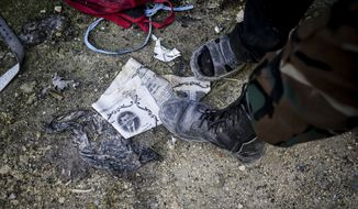 A Free Syrian Army fighter steps on a paper with the photo of Syrian President Bashar Assad in Aleppo, Syria, Tuesday, Jan. 15, 2013. (AP Photo/Andoni Lubaki)
