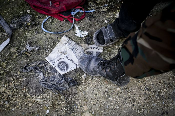 A Free Syrian Army fighter steps on a paper with the photo of Syrian President Bashar Assad in Aleppo, Syria