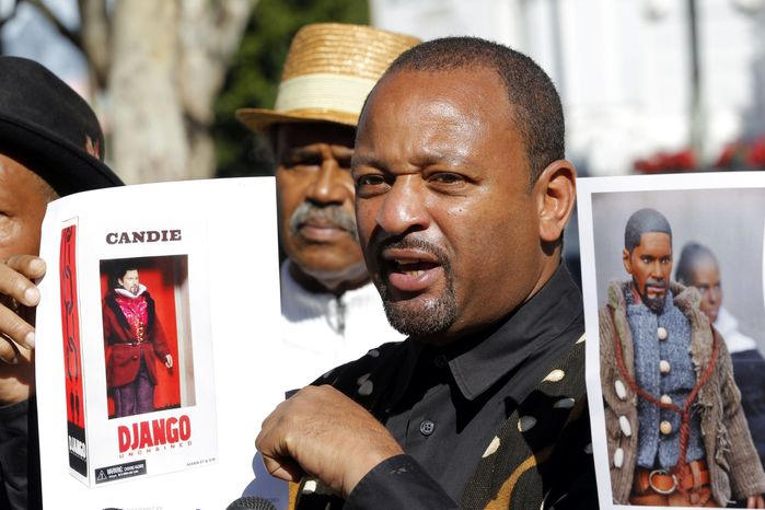 """Community activist Najee Ali holds an action figure depicting Calvin Candie, Leonardo DiCaprio's character from the Quentin Tarantino film """"Django Unchained,"""" during a news conference on Jan. 8, 2013 in Los Angeles. The slavery-era figures are raising questions about whether they're appropriate. Ali, director of the advocacy group Project Islamic Hope, plans to call for the removal of the toys from the market, calling the action figures """"a slap in the face of our ancestors."""" (Associated Press)"""