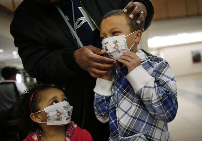 **FILE** Damien Dancy puts masks on his children Damaya (left), 3, and Damien, 7, at Sentara Princess Anne Hospital in Virginia Beach, Va., on Jan. 9, 2013, as hospitals in Hampton Roads urged patients and visitors to wear a mask at their facilities to help stop the spread of the flu. (Associated Press/The Virginian-Pilot)
