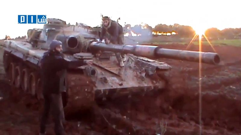 In this photo taken Jan. 10, 2013, from video obtained from the Shaam News Network, which has been authenticated based on its contents and other AP reporting, rebel fighters commandeer a captured Syrian Army tank in Taftanaz, in the Idlib province of northern Syria. (Associated Press/Shaam News Network via AP video)