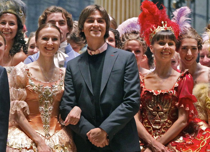 **FILE** Sergei Filin (center) poses Sept. 20, 2011, with members of the Bolshoi Theater company involved in the Sleeping Beauty ballet after a rehearsal at the Bolshoi Theater in Moscow. (Associated Press)