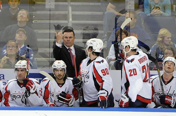Washington Capitals coach Adam Oates, center, signals from the bench during the first period of the Capitals' NHL hockey game against the Tampa Bay Lightning on Saturday, Jan. 19, 2013, in Tampa, Fla. (AP Photo/Brian Blanc