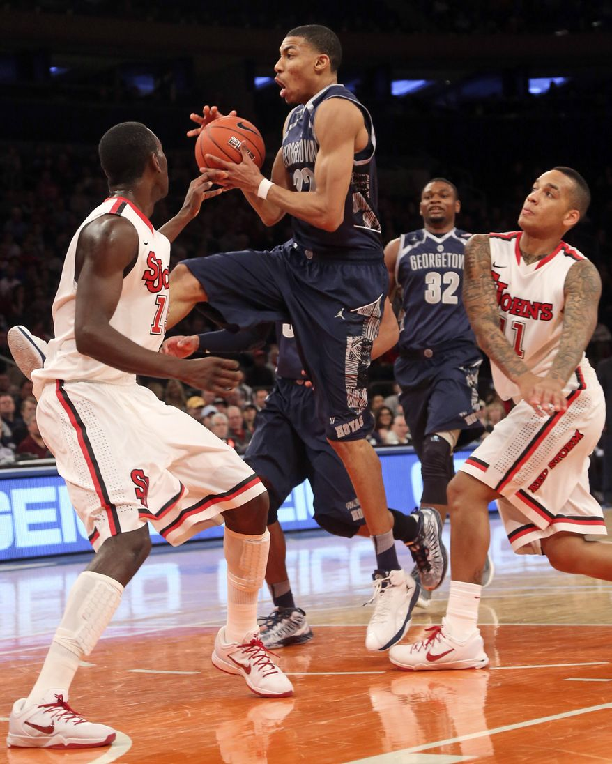 FILE -- Georgetown's Otto Porter Jr., center goes up against St. Johns' Sir Dominic Pointer, left, and D'angelo Harrison during the first half of an NCAA college basketball game, Saturday, Jan. 12, 2013, at Madison Square Garden in New York. Porter had 19 points and a season-high 14 rebounds and No. 19 Georgetown broke out of its scoring funk with a 67-51 victory. (AP Photo/Mary Altaffer)