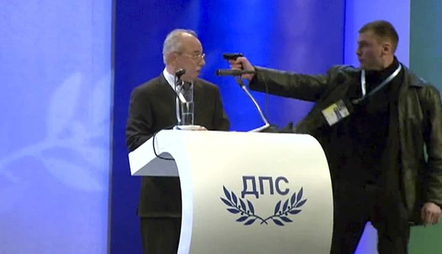 Image grab from video shows a man identified as Oktai Enimehmedov, 25, as he points a weapon at Ahmed Dogan, left, leader of the Movement for Rights and Freedoms, during his speech at his party's congress in Sofia, on Saturday, Jan. 19, 2013. Dogan struck the man before other delegates wrestled the assailant to the ground, and no shots were fired. Police took the man away.(AP Photo/ BTVnews)