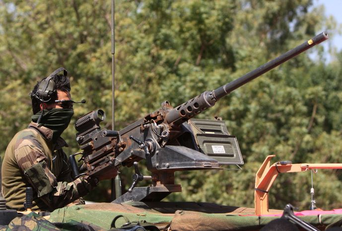 A French soldier mans a machine gun as French troops pass through San in central Mali en route to Sevare, Friday, Jan. 18, 2013. (AP Photo/Harouna Traore)