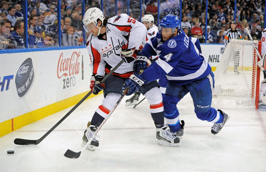 Tampa Bay Lightning center Vincent Lecavalier, right, makes a play for the puck against Washington Capitals defenseman Mike Green during the second period of an NHL hockey game Saturday, Jan. 19, 2013, in Tampa, Fla. (AP Photo/Brian Blanco)