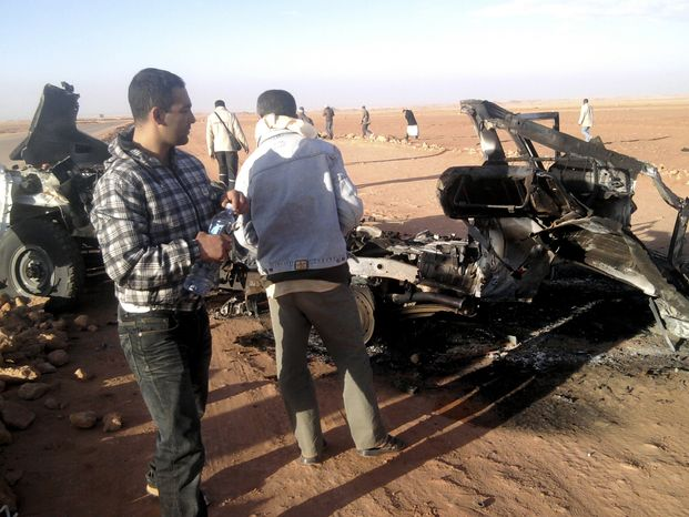 "Men look at the wreckage of a vehicle near the natural-gas plant in Ain Amenas, Algeria, in this undated photo. Algerian bomb squads on Sunday, Jan. 20, 2013, scoured the plant, where Islamist militants took dozens of foreign workers hostage, and found ""numerous"" new bodies as they searched for explosive traps"
