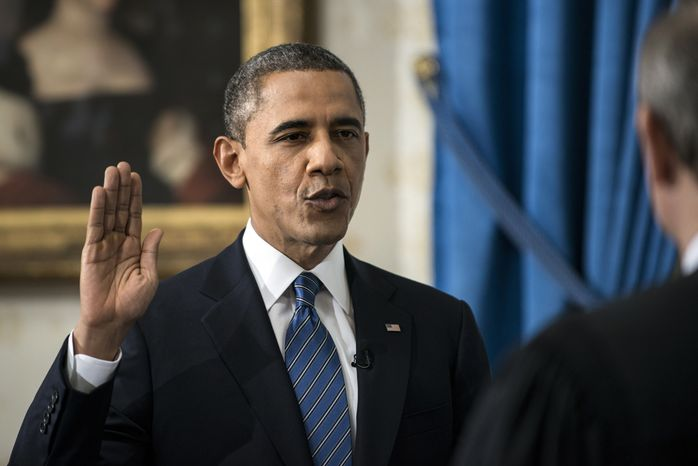 President Obama is officially sworn in by Chief Justice John G. Roberts Jr. in the Blue Room of the White House during the 57th Presidential Inauguration in Washington on Sunday, Jan. 20, 2013. (AP Photo/Brendan Smialowski, Pool)