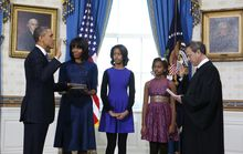 President Obama is officially sworn in by Chief Justice John G. Roberts Jr. (right) in the Blue Room of the White House in Washington on Sunday, Jan. 10, 2013. Next to Mr. Obama are first lady Michelle Obama, holding the Robinson family Bible, and daughters Malia and Sasha. (AP Photo/Larry Downing, Pool)