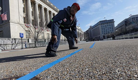 Worker Rodney Hart, prepares the street on Pennsylvania Avenue in front of the White House, Sunday, Jan. 20, 2013, in Washington. Thousands will march during the 57th Presidential Inauguration parade after the ceremonial swearing-in of President Barack Obama on Monday. (AP Photo/Gerald Herbert)