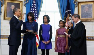 President Barack Obama is officially sworn-in by Chief Justice John Roberts in the Blue Room of the White House during the 57th Presidential Inauguration in Washington, Sunday Jan. 10, 2013. Next to Obama are first lady Michelle Obama, holding the Robinson Family Bible, and daughters Malia and Sasha. (AP Photo/Larry Downing, Pool)