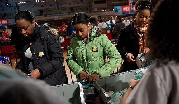 Volunteer Ayana Burrowes], 13, of Greenbelt, Md., center, puts together a service package for members of the armed services abroad during the National Day of Service at the D.C. Armory, Washington, D.C., Saturday, January 19, 2013. Non-profit groups are running hundreds of service projects for the Martin Luther King Jr. weekend. (Andrew Harnik/The Washington Times)