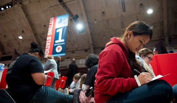 George Washington University Student Priscilla Nei, right, and dozens of other volunteers write handwritten letters to service members to go along with service packages for members of the armed services abroad during the National Day of Service at the D.C. Armory, Washington, D.C., Saturday, January 19, 2013. Non-profit groups are running hundreds of service projects for the Martin Luther King Jr. weekend. (Andrew Harnik/The Washington Times)