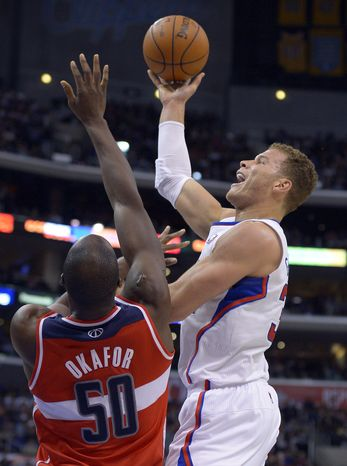 Los Angeles Clippers forward Blake Griffin, right, puts up a shot against Washington Wizards center Emeka Okafor during the first half of their NBA basketball game, Saturday, Jan. 19, 2013, in Los Angeles. (AP Photo/Mark J. Terrill)
