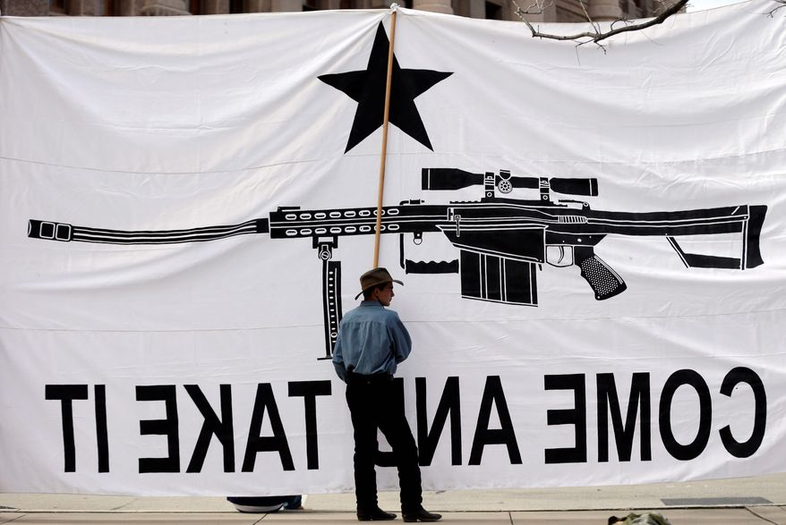 Austin Ehlinger helps hold a banner during a Guns Across America rally at the Texas state Capitol, Saturday, Jan. 19, 2013, in Austin, Texas. (AP Photo/Eric Gay)