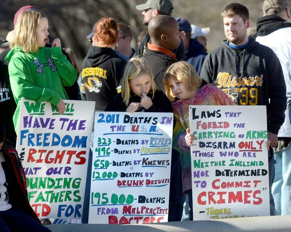 Friends (from left) Ella Sikes,10, Macey Seabaugh, 9, and Zoe Sikes, 7, of Fredericktown, Mo., hold signs they made for a gun-rights rally Saturday outside the capitol building in Jefferson City, Mo. Second Amendment advocates gathered in state capitals nationwide just days after President Obama announced a sweeping package of federal gun-control proposals. (The Jefferson City (Mo.) News-Tribune via Associated Press)