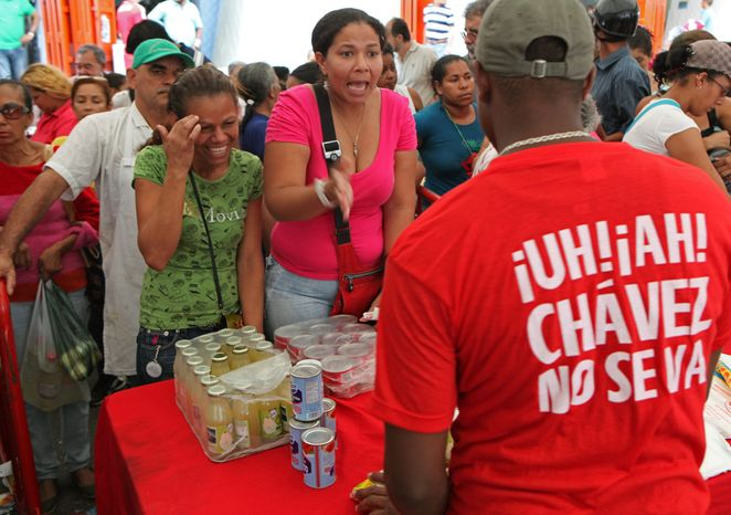 "Venezuelans swarm a government market in Caracas to buy subsidized food from a worker whose shirt translates as ""Oh no! Chavez isn't leaving."" (Associated Press)"