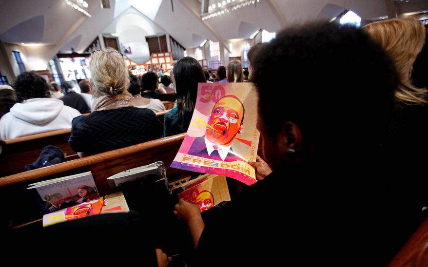"Volunteers roll up posters marking the 50th anniversary of Martin Luther King Jr.'s ""I Have a Dream"" speech during the annual commemorative service in his honor at the Ebenezer Baptist Church in Atlanta. Americans on Monday honored the late civil rights leader on the same day as they celebrated the second-term inauguration of the nation's first black president. (Associated Press)"