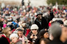 The crowds along the parade route from Capitol Hill to the White House were large and largely happy, including a man who rose above the throng before the swearing-in ceremony started. (Andrew Harnik/The Washington Times)