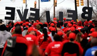 "A group carries letters spelling ""BELIEVE"" as they take part in a march honoring Martin Luther King Jr., on Monday in San Antonio. (Associated Press)"