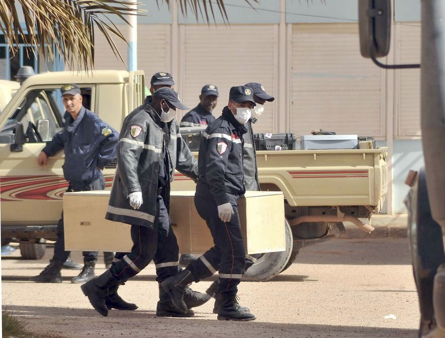 Algerian firemen carry a coffin containing a person killed during the gas-facility hostage situation at the morgue in Ain Amenas, Algeria, on Monday, Jan. 21, 2013. (AP Photo/Anis Belghoul)