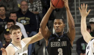 Georgetown forward Mikael Hopkins (3) throws a pass around Notre Dame forward Jack Cooley during the first half of Georgetown's 63-47 win on Jan. 21, 2013, in South Bend, Ind. (Associated Press)