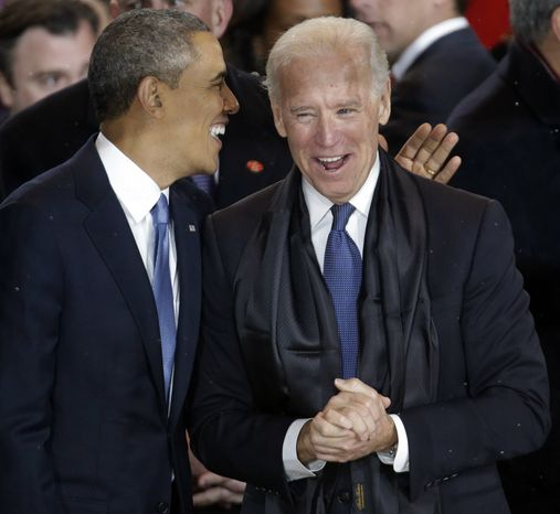 President Obama talks with Vice President Joseph R. Biden in the presidential box during the inaugural parade down Pennsylvania Avenue en route to the White House on Jan. 21, 2013. (Associated Press)