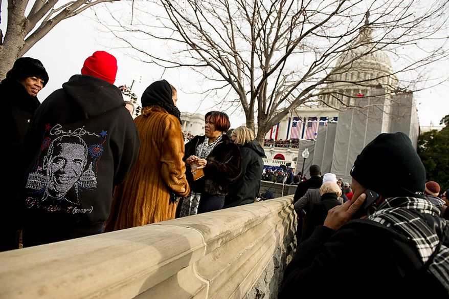 Members of the crowd wait for President Barack Obama to be sworn in for his second term on the West Lawn of the U.S. Capitol Building at the 57th Presidential Inauguration Ceremony, Washington, D.C., Monday, January 21, 2013. (Andrew Harnik/The Washington Times)